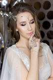 Gentle portrait of a beautiful cute happy bride with a beautiful hairdo festive bright make-up in a wedding dress with earrings an. D a ring with an ornament in Royalty Free Stock Photography