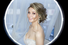 Gentle portrait of a beautiful cute happy bride with a beautiful hairdo festive bright make-up in a wedding dress with earrings an. D a ring with an ornament in Stock Images