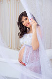 Gentle pregnancy. Beautiful pregnant in light white dress with orchids Royalty Free Stock Photography