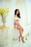 Gentle pregnancy. Beautiful pregnant in light white lace negligee in the bathroom royalty free stock image