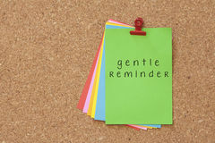 Gentle Reminder written on color sticker notes over cork board b royalty free stock photography