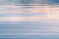 Abstract background of ripples in water reflecting sunset colors in sky royalty free stock photography