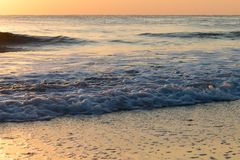 Gentle rolling waves breaking on peaceful empty beach at sunrise. Brightly lit seascape background with golden colored gentle breaking sea waves lapping on the Royalty Free Stock Photography