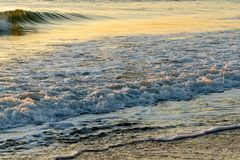 Gentle rolling waves breaking on peaceful empty beach at sunrise. Brightly lit seascape background with golden colored gentle breaking sea waves lapping on the Stock Photos