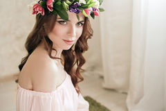 Gentle romantic appearance of the girl with a wreath of roses on her head and a pink dress. Joyful Jolly spring woman. Summer lady Royalty Free Stock Photos