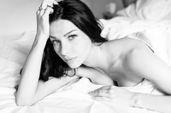 Gentle romantic seductive young woman lying in bed & looking at camera white background black & white image stock photography