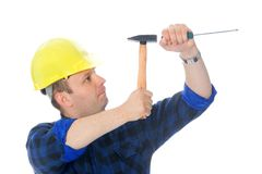 Gentle screwdriver hammering. Worker is hitting screwdriver with hammer and have face expression of real master Royalty Free Stock Photography