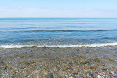 Gentle Sea surf on a beach of pebbles, horizon and blue sky, fro. Gentle sea surf on a beach of pebbles on the shore of the Baltic Sea, horizon and blue sky stock photos
