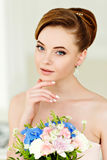 Gentle, sensual portrait of very beautiful girls bride blonde in. A pink dress and veil with a bouquet of flowers in his hands, a bright interior Stock Image
