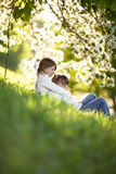 Gentle sisters hug apple blossom, sunny childhood Stock Photo