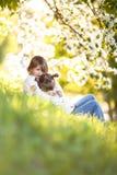 Gentle sisters hug apple blossom, sunny childhood Stock Photos