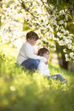 Gentle sisters hug apple blossom, sunny childhood Royalty Free Stock Photos