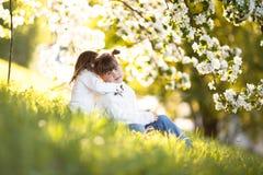 Gentle sisters hug apple blossom, sunny childhood. Delicate girls sisters hug around the branches of apple blossom, bright, sunny childhood, spring concept Royalty Free Stock Photo