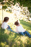 Gentle sisters hug apple blossom, sunny childhood Royalty Free Stock Image