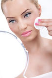 Gentle skincare for a great complexion. Young woman looking at her complexion in the mirror and cleaning her skin with cotton pad stock photos
