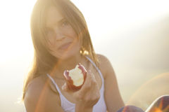 Gentle smile. Beautiful young woman eating a red apple in bight sun Royalty Free Stock Images