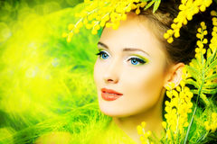 Gentle smile. Portrait of a beautiful girl with mimosa flowers. Spring Stock Photography