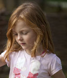 Gentle Smile. A young girl with ginger hair is smiling gently while thinking something pleasant. She is looking down and her hair frames her face royalty free stock images