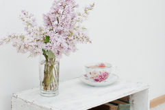 Gentle spring bouquet and tea. Gentle spring bouquet of lilac and tea in china teacup with victorian roses on vintage shabby nightstand Stock Photo