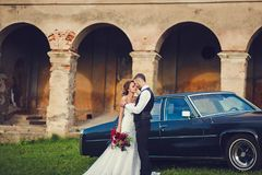 Gentle stylish groom and bride. On the background old fashioned car and building Stock Photography