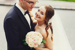 Gentle stylish sgroom and bride holding boucuet of creamy roses Royalty Free Stock Photo