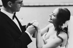 Gentle stylish sgroom and bride holding hands Stock Photos