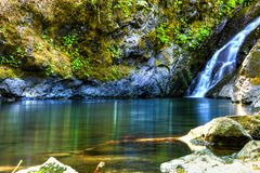 Gentle waterfall pours into a clean clear pool of water close to a hiking trail on the Rogue River in Oregon. Gentle waterfall pours into a clean pool of water stock photos