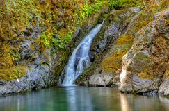 Gentle waterfall pours into a clear pool of water in Rogue River Oregon. Gentle waterfall pours into a clean clear pool of water in Rogue River Oregon stock photo