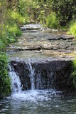 Gentle Waterfall. Slow moving stream gently flows over the hidden ledge creating a small but perfect waterfall as the water bubbles in the pool below as the Royalty Free Stock Photo
