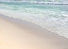 Gentle wave ripples of blue ocean on sandy beach Stock Image
