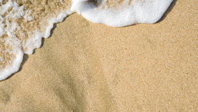 Gentle wave washes over beach sand Royalty Free Stock Photo