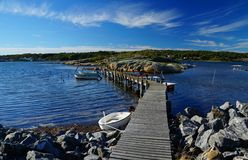Gentle waves, bare rocks and a wooden pier between two islands. Wooden pier with small, moored ships between bare rocks on the seaside of Donsö, an island of Royalty Free Stock Photo