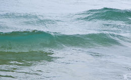 Gentle waves on a calm sea. Gentle waves splashing on a calm sea on a overcast day Royalty Free Stock Photo