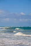 Gentle Waves on the Caribbean Sea. Waves breaking on the shore at the Cabarete Bay, Cabarete, Dominican Republic with blue sky Royalty Free Stock Images