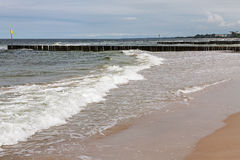 Gentle waves in the waters of the Baltic Sea. The gentle waves of the waters of the Baltic Sea reaches the sandy beach in Kolobrzeg in Poland Royalty Free Stock Images