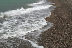 Gentle waves with white foam washed sea coast. Covered with small pebbles Royalty Free Stock Photo