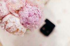 Gentle wedding bouquet peonies with rings background. Gentle wedding bouquet peonies with wedding rings top view Royalty Free Stock Image