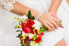 Gentle wedding bouquet of roses in hands. Of the bride, bracelet of pearls Royalty Free Stock Photography