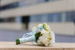 Gentle wedding bouquet. On a stone parapet in the background of a modern building. White and blue flowers tied with blue ribbon and white lace Royalty Free Stock Images