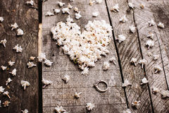 Gentle white heart shape flowers with ring on wood table Royalty Free Stock Image