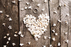 Gentle white heart shape flowers with ring on wood table Stock Photography
