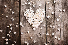 Gentle white heart shape flowers with ring on wood table Stock Image