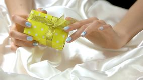 Gentle winter manicure and gift box. Young woman well-groomed hands is unpacking yellow dotted box with gift. Holidays and celebrations concept stock video