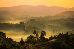 Gentle yellow light and light mist over the hills in country side with traditional houses and the tropical nature of Uganda stock photography