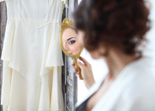 Gentle young bride looks in the mirror Stock Image