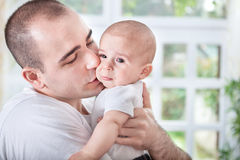Gentle young father comforting crying baby Stock Photo