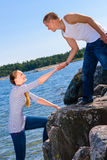 Gentleman. Young gentleman helping her girlfriend to climb on rocks Stock Image