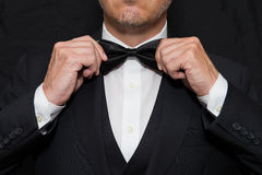 Gentleman in Black Tie Straightens His Bowtie. Close-up of a gentleman wearing Black Tie straightens his bowtie Royalty Free Stock Photo
