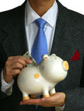 A gentleman deposits money into the piggy bank Stock Photos