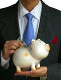 A gentleman deposits money into the piggy bank. A gentleman deposits some money into the piggy bank Stock Photos
